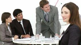 Κλείστε επάνω της ελκυστικής επιχειρηματία στο γραφείο με τους συναδέλφους της απόθεμα βίντεο