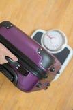 Κλείστε επάνω της ζυγίζοντας βαλίτσας γυναικών στην κλίμακα πριν από τις διακοπές Στοκ εικόνες με δικαίωμα ελεύθερης χρήσης