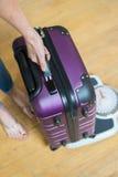 Κλείστε επάνω της ζυγίζοντας βαλίτσας γυναικών στην κλίμακα πριν από τις διακοπές Στοκ φωτογραφίες με δικαίωμα ελεύθερης χρήσης