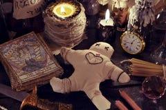Κλείστε επάνω της κούκλας woodoo, του μαχαιριού, των καίγοντας κεριών και των μαγικών αντικειμένων Στοκ εικόνες με δικαίωμα ελεύθερης χρήσης