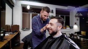 Κλείστε επάνω της μοντέρνης συνεδρίασης ατόμων χαμόγελου γενειοφόρου που καλύπτεται με το μαύρο peignoir στο barbeshop Ο κουρέας  φιλμ μικρού μήκους