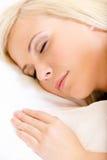 Κλείστε επάνω της νυσταλέας γυναίκας στο κρεβάτι στοκ εικόνα