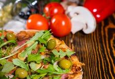 Κλείστε επάνω της νόστιμης πίτσας με το arugula και των ελιών στον ξύλινο πίνακα Στοκ Εικόνα