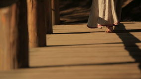 Κλείστε επάνω της ξυπόλυτης γυναίκας στο πολύ κεντημένο παραδοσιακό φόρεμα που περπατά στην ξύλινη γέφυρα Carpathians απόθεμα βίντεο