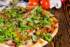 Κλείστε επάνω της πίτσας με το arugula και των ελιών στον ξύλινο πίνακα Στοκ φωτογραφίες με δικαίωμα ελεύθερης χρήσης
