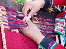 Κλείστε επάνω της περουβιανής κυρίας στο αυθεντικό περιστρεφόμενο νήμα φορεμάτων από το εκτάριο Στοκ Εικόνες