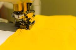 Κλείστε επάνω της ράβοντας μηχανής κάνοντας τη διπλή βελονιά με το μαύρο νήμα στο κίτρινο ύφασμα Στοκ Φωτογραφίες