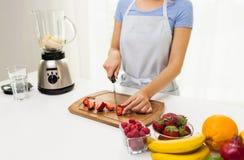 Κλείστε επάνω της τεμαχίζοντας φράουλας γυναικών στο σπίτι Στοκ Φωτογραφία