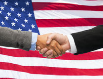 Κλείστε επάνω της χειραψίας πέρα από τη αμερικανική σημαία Στοκ Φωτογραφία