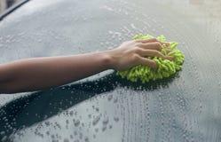Κλείστε επάνω τη λαβή χεριών γυναικών μια πλύση βουρτσών πέρα από τον ανεμοφράκτη του αυτοκινήτου, η γυναίκα μπορεί να πλύνει την Στοκ Εικόνες