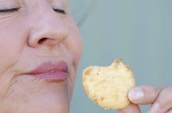 Κλείστε επάνω τη γυναίκα δαγκώνοντας τις γλυκές ιδιαίτερες πρόχειρο φαγητό προσοχές μπισκότων στοκ εικόνες