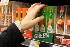 Κλείστε επάνω τη γυναίκα που αγοράζει την πράσινη σάλτσα πιπεριών Tabasco Στοκ φωτογραφία με δικαίωμα ελεύθερης χρήσης