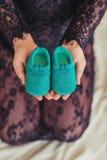 Κλείστε επάνω τη γυναίκα σχετικά με τα παπούτσια μωρών εκμετάλλευσης Στοκ Εικόνα