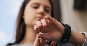 Κλείστε επάνω τη γυναίκα χρησιμοποιώντας το smartwatch της, έξυπνος app συσκευών συσκευών χεριών κινηματογραφήσεων σε πρώτο πλάνο απόθεμα βίντεο