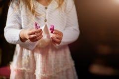 Κλείστε επάνω τη λεπτομέρεια των χεριών κοριτσιών ` s μικρών παιδιών που παίζει με ένα μικρό λουλούδι Στοκ εικόνα με δικαίωμα ελεύθερης χρήσης