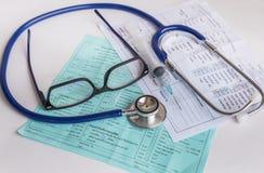 Κλείστε επάνω τη σύριγγα βελόνων και το ιατρικό στηθοσκόπιο με τα γυαλιά σε χαρτί συνταγών διαγραμμάτων αίματος Στοκ φωτογραφία με δικαίωμα ελεύθερης χρήσης