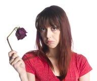 Κλείστε επάνω τη λυπημένη εκμετάλλευση γυναικών νεκρή αυξήθηκε λουλούδι στοκ φωτογραφία