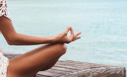 Κλείστε επάνω τη χειρονομία χεριών της γυναίκας που κάνει μια υπαίθρια θέση γιόγκας Lotus στοκ εικόνες με δικαίωμα ελεύθερης χρήσης