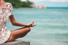 Κλείστε επάνω τη χειρονομία χεριών της γυναίκας που κάνει μια υπαίθρια θέση γιόγκας Lotus στοκ φωτογραφία