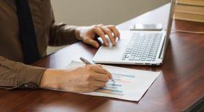 Κλείστε επάνω τον επιχειρηματία που αναλύει το έγγραφο γραφικών παραστάσεων με το lap-top στην αρχή Στοκ φωτογραφία με δικαίωμα ελεύθερης χρήσης