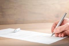 Κλείστε επάνω τον επιχειρηματία που υπογράφει ένα έγγραφο συμβάσεων Στοκ Εικόνες