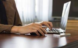 Κλείστε επάνω τον επιχειρηματία χρησιμοποιώντας την εργασία lap-top στην αρχή με το τηλέφωνο κυττάρων Στοκ φωτογραφία με δικαίωμα ελεύθερης χρήσης