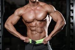 Κλείστε επάνω τον ισχυρό τύπο ABS που παρουσιάζει στους μυς γυμναστικής Στοκ Εικόνες