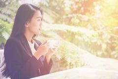 Κλείστε επάνω τον καφέ κατανάλωσης γυναικών στη καφετερία για την περίληψη της έκθεσης επιχειρησιακής απόδοσης στοκ εικόνα