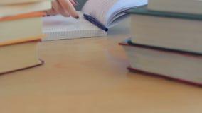 Κλείστε επάνω τον πίνακα με το σωρό των βιβλίων Ο σπουδαστής έρχεται, αρχίζει τη μελέτη, παίρνοντας τις σημειώσεις φιλμ μικρού μήκους