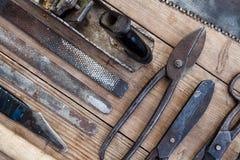 Κλείστε επάνω τον τρύγο άποψης οξύδωσε τα εργαλεία στον παλαιό ξύλινο πίνακα: πένσες, γαλλικό κλειδί σωλήνων, κατσαβίδι, σφυρί, ψ Στοκ Εικόνα