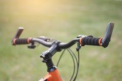 Κλείστε επάνω τους φραγμούς λαβών ποδηλάτων θόλωσε το πράσινο υπόβαθρο στοκ φωτογραφίες