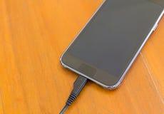 Κλείστε επάνω του έξυπνου τηλεφώνου χρεώνοντας με το καλώδιο USB Στοκ φωτογραφίες με δικαίωμα ελεύθερης χρήσης