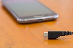 Κλείστε επάνω του έξυπνου τηλεφώνου χρεώνοντας με το καλώδιο USB Στοκ εικόνα με δικαίωμα ελεύθερης χρήσης