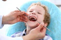 Κλείστε επάνω του αγοριού που έχει τα δόντια του εξετασμένων από έναν οδοντίατρο στοκ εικόνα