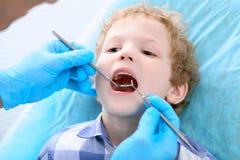 Κλείστε επάνω του αγοριού που έχει τα δόντια του εξετασμένων από έναν οδοντίατρο στοκ εικόνες