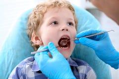 Κλείστε επάνω του αγοριού που έχει τα δόντια του εξετασμένων από έναν οδοντίατρο Στοκ Φωτογραφία