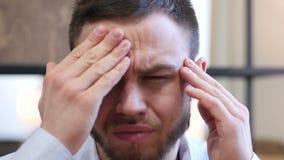 Κλείστε επάνω του ανήσυχου νεαρού άνδρα με τον πονοκέφαλο απόθεμα βίντεο
