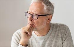 Κλείστε επάνω του ανώτερου ατόμου στη σκέψη γυαλιών στοκ εικόνες