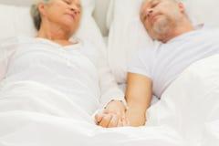 Κλείστε επάνω του ανώτερου ύπνου ζευγών σε κακό στο σπίτι Στοκ Εικόνες