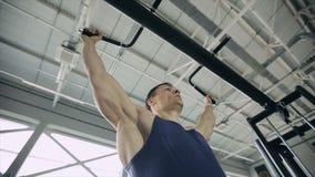 Κλείστε επάνω του αρσενικού bodybuilder σηκώνοντας σε μια γυμναστική κίνηση αργή φιλμ μικρού μήκους