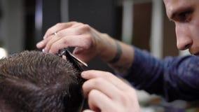 Κλείστε επάνω του αρσενικών κεφαλιού και των χεριών των τεμνουσών ακρών τρίχας hairstylist του πελάτη του χρησιμοποιώντας το αιχμ φιλμ μικρού μήκους