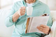 Κλείστε επάνω του ατόμου με την κατανάλωση περιοδικών από το φλυτζάνι Στοκ Εικόνες