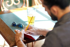 Κλείστε επάνω του ατόμου με την μπύρα και του σημειωματάριου στο μπαρ Στοκ Εικόνα