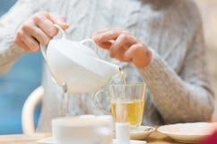 Κλείστε επάνω του ατόμου με το χύνοντας τσάι δοχείων στον καφέ Στοκ εικόνα με δικαίωμα ελεύθερης χρήσης