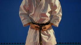 Κλείστε επάνω του ατόμου που εμπλέκει έναν κόμβο της μαύρης ζώνης στον ειδικό karate εξοπλισμό κιμονό σε σε αργή κίνηση απόθεμα βίντεο