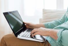 Κλείστε επάνω του ατόμου που εργάζεται με το lap-top στο σπίτι Στοκ Εικόνα