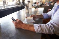 Κλείστε επάνω του ατόμου που ελέγχει τα μηνύματα στο τηλέφωνο στη καφετερία στοκ εικόνα