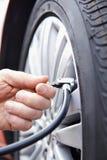 Κλείστε επάνω του ατόμου που διογκώνει το ελαστικό αυτοκινήτου αυτοκινήτων με τη γραμμή πίεσης αέρα Στοκ Φωτογραφία