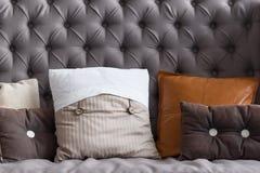 Κλείστε επάνω του γκρίζου εκλεκτής ποιότητας καναπέ με τα μαξιλάρια Στοκ Εικόνες