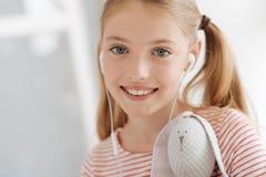 Κλείστε επάνω του γκρίζου eyed κοριτσιού με το παιχνίδι που απολαμβάνει τη μουσική Στοκ Εικόνες